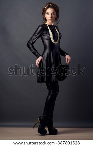 Beautiful young woman. Young girl. Girl in leather clothes. Portrait on a dark background. Beauty portrait. Toned image