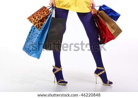 Beautiful, young, womans legs with colorful shopping bags in her hand - stock photo