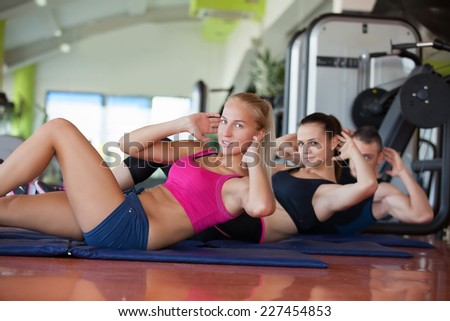 beautiful young women and man working out in the fitness studio