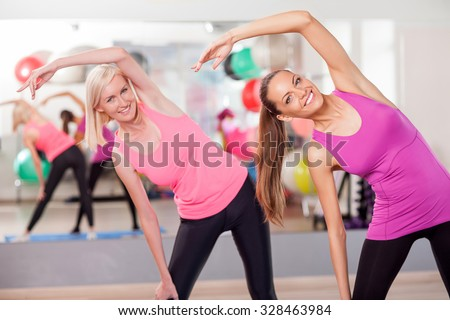 Beautiful young women are doing exercise in gym. They are standing and looking at camera with happiness. The ladies are smiling - stock photo