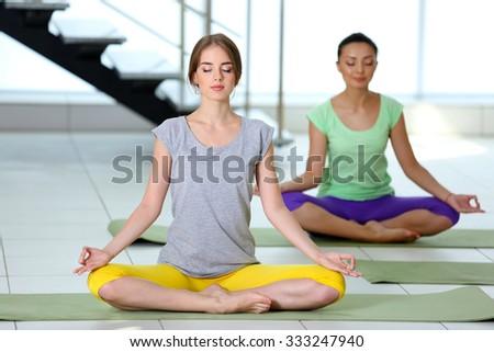 Beautiful young women do yoga - stock photo