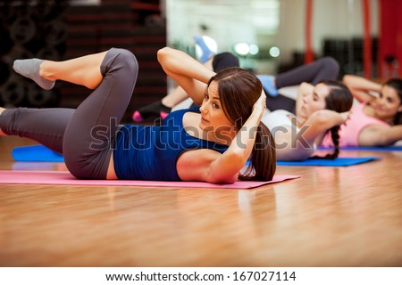 Beautiful young women doing crunches during a class at a gym - stock photo