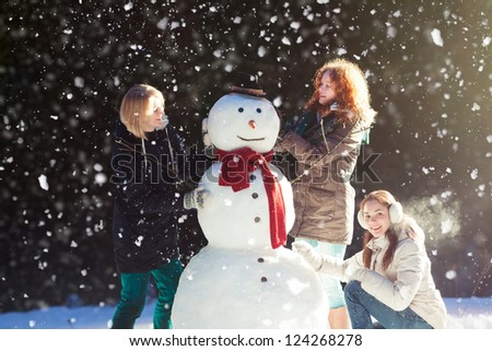 Beautiful young women enjoying building a snowman on a snowy winter day in forest - stock photo