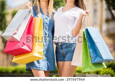 Beautiful young women enjoying shopping, holding colored bags, close-up. - stock photo