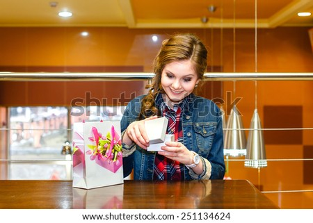Beautiful young women in the cafe opens and joyfully looks in a white gift box - stock photo