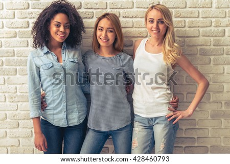Beautiful young women of different nationalities are looking at camera and smiling, standing against white brick wall