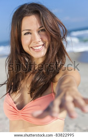 Beautiful young women or girl in bikini on a sunny beach smiling and reaching hand to the camera