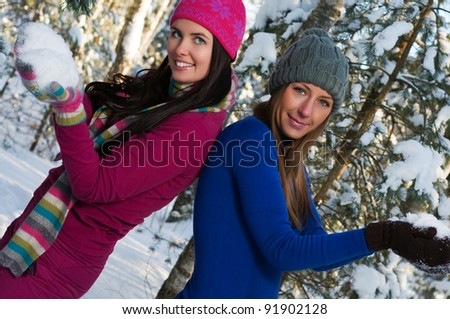 Beautiful young women outdoor in winter playing snowballs - stock photo