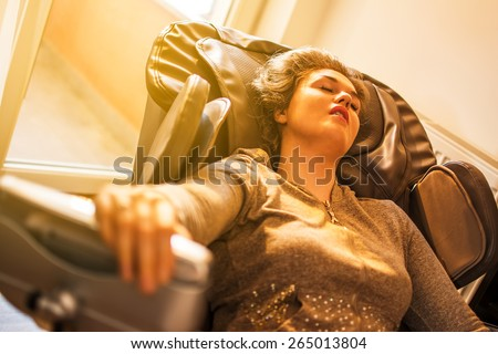 Beautiful young women relaxing on the massage chair in living room. - stock photo