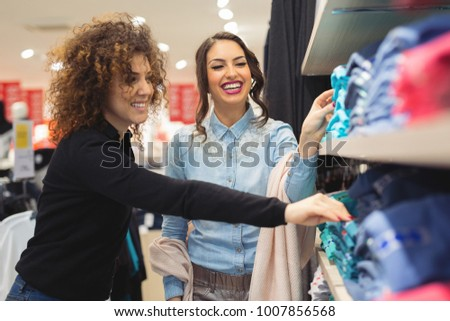Beautiful young women shopping in a boutique for clothes. Young beautiful women at the weekly cloth market.