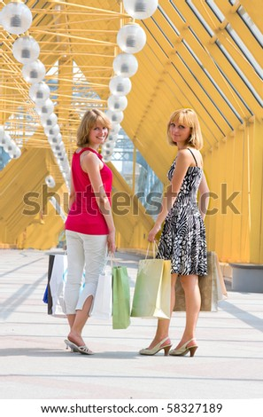 Beautiful young women shopping. Young woman holding several bags in shopping centre. Two friends on a shopping tour in the city