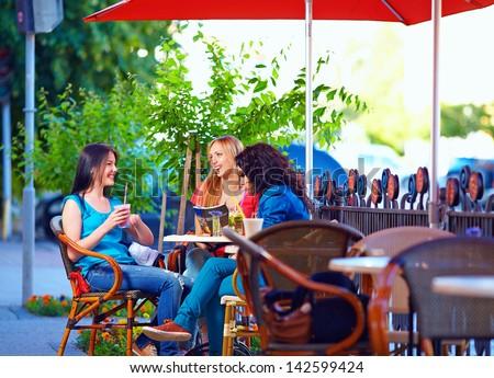 beautiful young women sitting on cafe terrace - stock photo