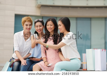Beautiful young women sitting outdoors and using smartphone