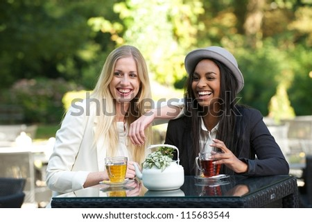 Beautiful young women smiling and drinking tea at an outdoors cafe - stock photo