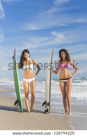 Beautiful young women surfer girls in bikinis with surfboards on a beach - stock photo