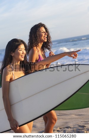 Beautiful young women surfer girls in bikinis with surfboards on a beach at sunset or sunrise - stock photo