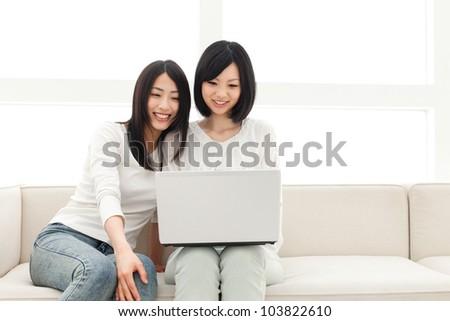 Beautiful young women using a laptop computer. Portrait of asian - stock photo