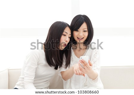 Beautiful young women using a moblie phone. Portrait of asian. - stock photo
