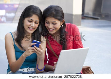 Beautiful young women using cell phone - stock photo