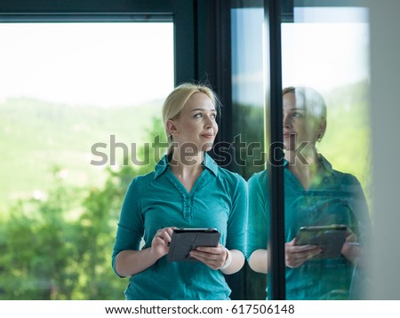beautiful young women using tablet computer by the window  of her luxury home