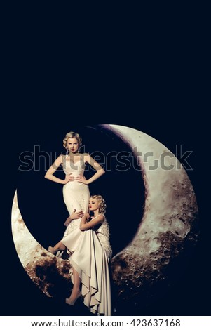 Beautiful young women with blonde hair and red lips posing on crescent moon in long evening elegant dress white color on black background