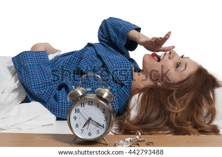 Beautiful young yawning woman waking up with an alarm clock - stock photo