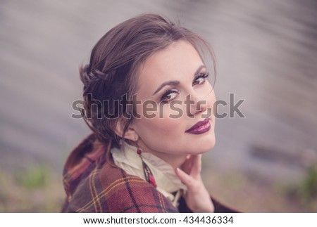 Beautiful younger girl with a vintage hairstyle and makeup professional in the background of the lake in park, closeup portraits - stock photo