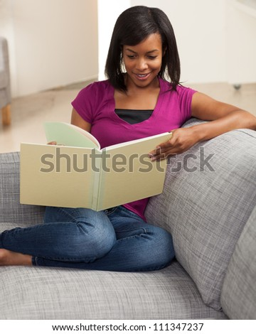 Beautiful youthful African American woman relaxing at home on grey couch wearing pink shirt.