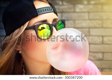 Beautiful yyoung woman blowing a bubble gum balloon - stock photo