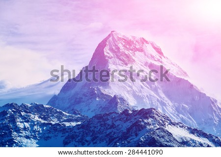 beautifull cloudy sunrise in the mountains with snow ridge - stock photo