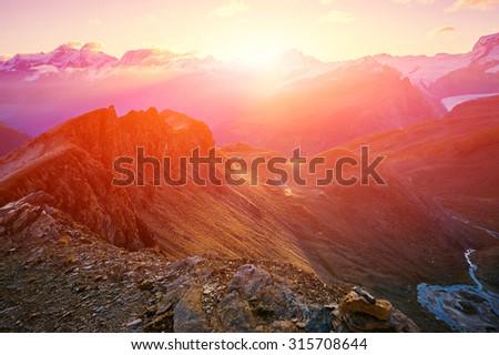 beautifull cloudy sunrise in the mountains with snow ridge. Alps. Switzerland, Trek near Matterhorn mount. - stock photo