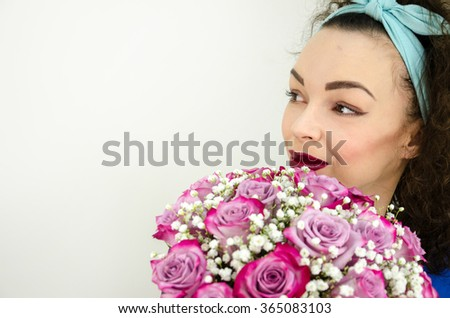 Beautifull woman holding arrangment of flowers