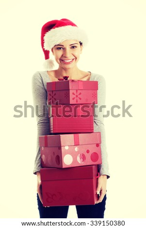 Beautifull woman in santa hat holding presents. Isolated on white.