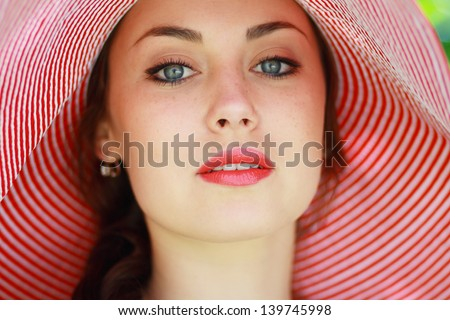 beautifull young brunette woman in bright summer hat close up on a warm summer day - stock photo