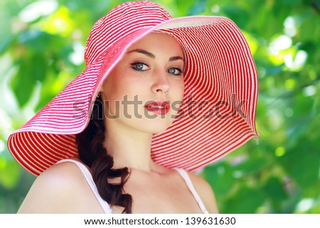 beautifull young brunette woman in bright summer hat on the meadow on a warm summer day - stock photo