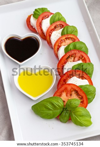 Beautifully arranged tomato slices with fresh basil and goat cheese served with oil and balsamic vinegar - stock photo