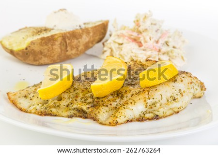 Beautifully baked fillet of cod sprinkled with mixture of herbs and spices on white plate with baked potato and coleslaw. - stock photo