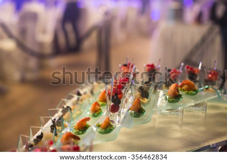Beautifully decorated banquet catering prepared table with different food snacks and appetizers with sandwich, caviar, fresh fruits on corporate christmas birthday party event or wedding celebration  - stock photo