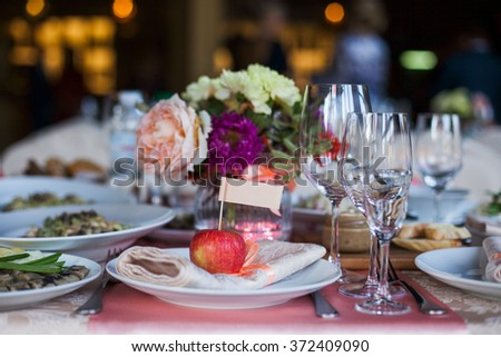 Beautifully decorated banquet table with flowers and different food snacks and appetizers with sandwich, wine glass, plate, apple on corporate event or wedding celebration - stock photo