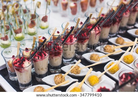 Beautifully decorated catering banquet prepared table with different food snacks and appetizers with sandwich, caviar, fresh fruits on corporate christmas birthday party event or wedding celebration