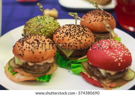 Beautifully decorated catering banquet table with different colored hamburgers burgers sandwiches on a plate on corporate christmas birthday party event or wedding celebration - stock photo