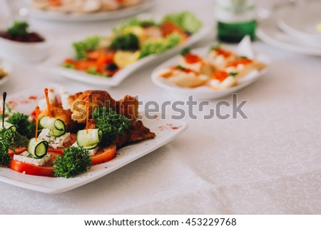 Beautifully decorated catering banquet table with different food snacks and appetizers