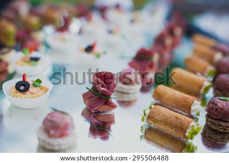 Beautifully decorated catering banquet table with different food snacks and appetizers with sandwich, caviar and fresh fruits on corporate party event or wedding celebration - stock photo