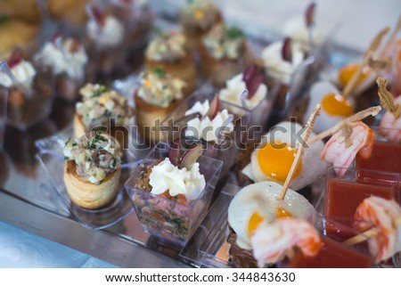 Beautifully decorated catering banquet table with different food snacks and appetizers with sandwich, caviar, fresh fruits on corporate christmas birthday party event or wedding celebration  - stock photo