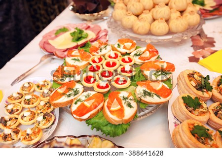 Beautifully decorated catering banquet table with different food snacks and appetizers with sandwich, caviar, fresh fruits  - stock photo
