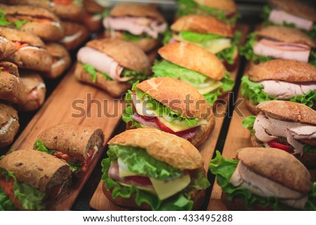 Beautifully decorated catering banquet table with different food snacks and appetizers with sandwich, on corporate christmas birthday kids party event or wedding celebration - stock photo