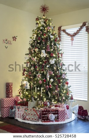 Beautifully decorated Christmas tree with gifts inside new home