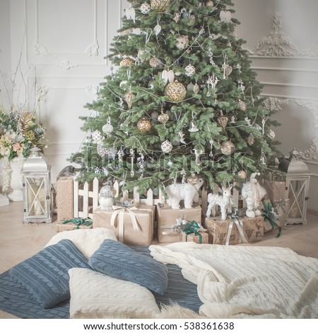 Beautifully decorated Christmas tree with presents. Feast of the Nativity. Blankets, pillows on the floor, a cozy place.