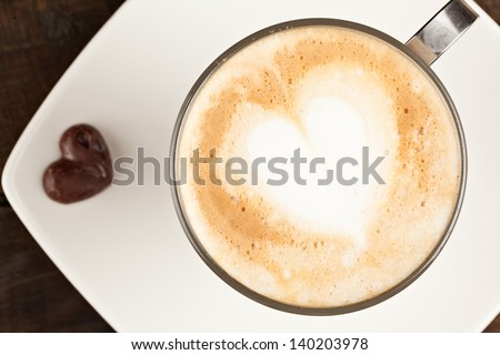 BEAUTIFULLY DECORATED CUP OF CAPPUCCINO AND CHOCOLATE HEART, AGAINST POLISHED TABLE TOP  - stock photo