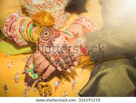 beautifully decorated Indian bride hands with the groom. - stock photo